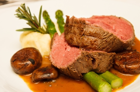 Rare prime rib beef on a plate with mushrooms, gravy, asparagus, potatoes and rosemary