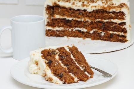Een stukje van de carrot cake op een bord met een vork. De helft taart op de achtergrond met kopje koffie