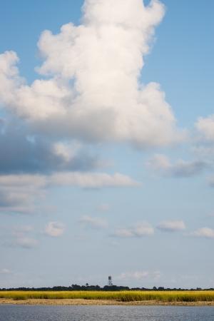 under fire: Un incendio en una torre costera de agua salada pantano bajo las nubes y el cielo