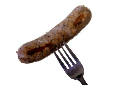 browned: A browned chicken sausage on a fork on white background