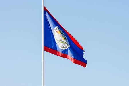 Flag of Belize blowing in the breeze against a clear blue sky