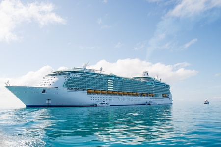 A huge luxury cruise ship anchored under nice skies on calm green water Archivio Fotografico