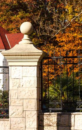 A decorative stone column on a black wrought iron fence around an estate in autumn Banco de Imagens
