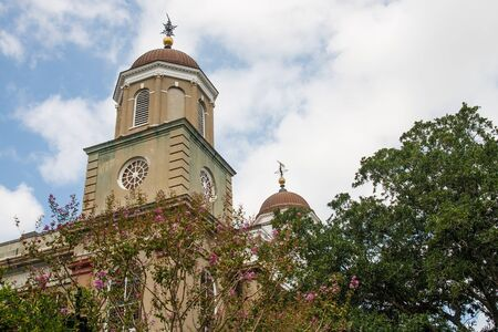 A classic church of brown stucco wtih domes steeples behind trees photo