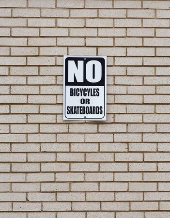A sign on a brick wall no bicycles or skateboards Stock Photo - 18263153