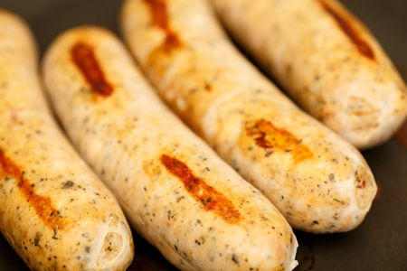 Four chicken sausages browning in a frying pan Stock Photo