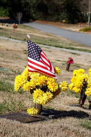 American flag and yellow chrysanthemums on grave in cemetery 版權商用圖片