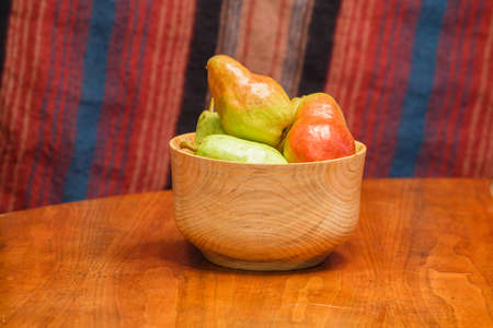 Fresh pears in a wood bowl on a wood table with a striped background Stock Photo - 18491396