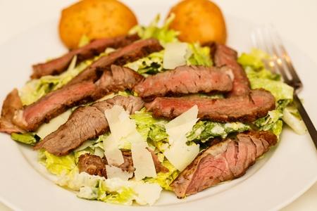 ensalada cesar: Una fresca ensalada César con tiras de carne medio raro y muffins dos Foto de archivo