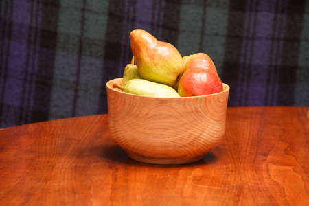 Fresh pears in a wood bowl on a wood table with a plaid background Stock Photo - 18491478