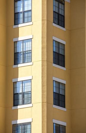 Las ventanas en esquina de una torre de apartamentos de estuco amarillo Foto de archivo - 18543944