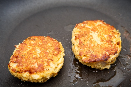 Two crab cakes browning in hot oil in a saute pan 版權商用圖片