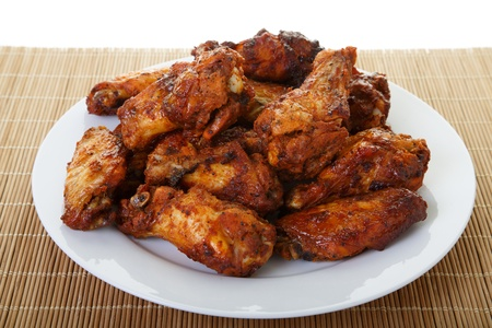 chicken wings: A white plate of spicy, mesquite flavored chicken wings