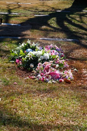 gravesite: Fresh flowers on a new gravesite in a cemetery