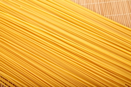 Closeup of strands of dry spaghetti on a bamboo mat Stok Fotoğraf