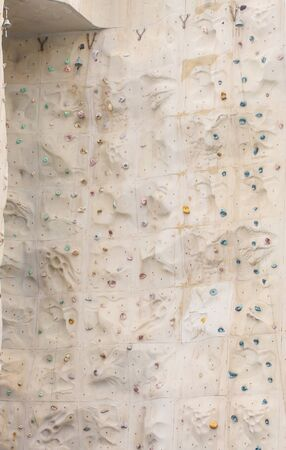 A climbing wall with a bell at the top corner to signal success Stock Photo