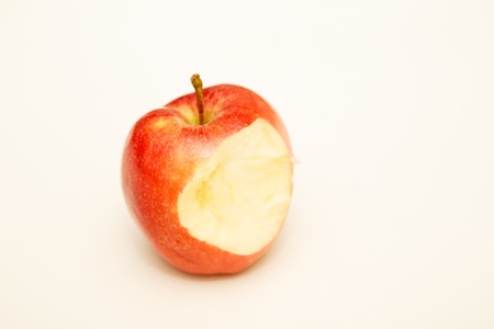 A single red apple on a white counter with bite missing