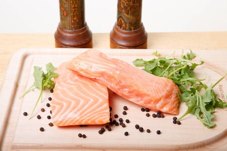 Two fresh, raw Atlantic salmon fillets with black peppercorns and arugula on a cutting board with pepper and slat grinders in background