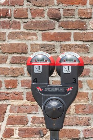 A pair of parking meters in front of a brick wall
