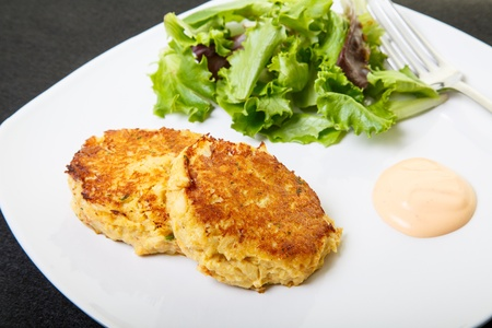 Fresh crab cakes on a white plate with sauce and a salad of field greens