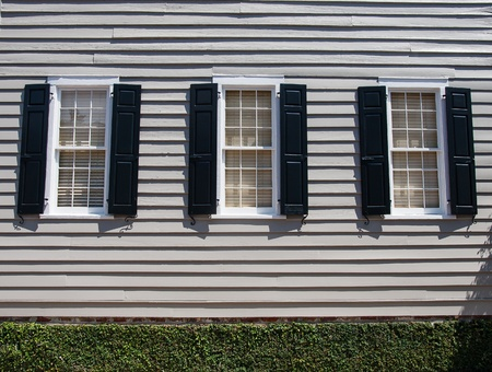 windows: Three windows in wood siding home with black shutters