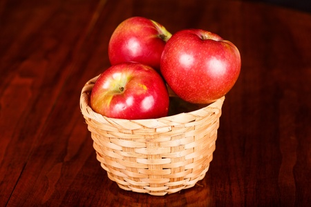 macintosh: Basket of red apples on a wood table Stock Photo