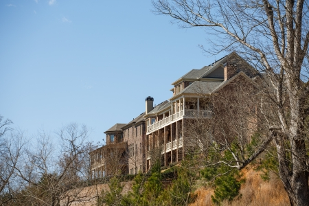 verandas: Two large brick homes with verandas on a hilltop under clear blue skies