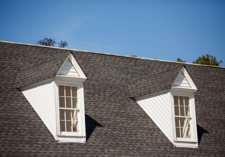 Twee witte houten dakkapellen op een grijze dakspaandak onder blauwe hemel Stockfoto