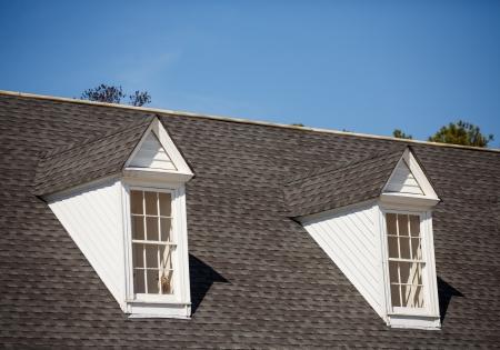gürtelrose: Zwei wei�e Holz Gauben auf einem grauen Schindeldach unter blauem Himmel