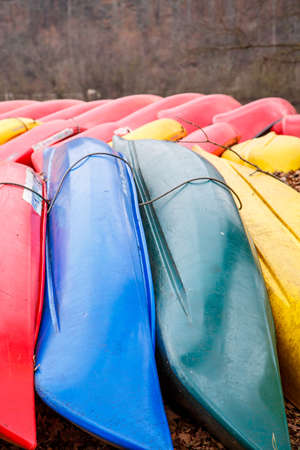 rentals: Many colored canoes on the shore of a river for rentals