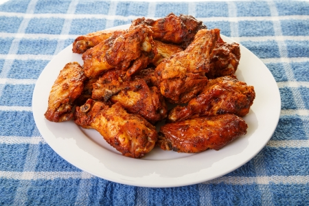 hot wings: A white plate of spicy, mesquite flavored chicken wings