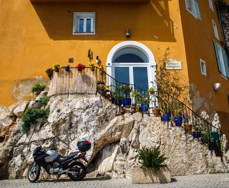 A modern motorcycle parked by an old stone staircase leading to an orange stucco villa photo