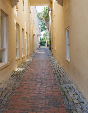 A narrow alley paved with bricks between yellow stucco walls