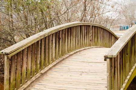 span: Odl wooden bridge curving over a small stream in a park