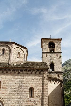 Old stone church and bell tower under blue sky in Kotor, Montenegro Stock fotó