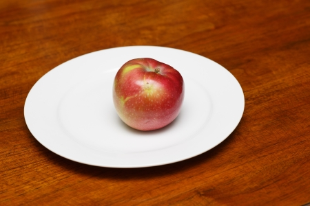 macintosh: A single red apple alone on an empty white plate and wood table
