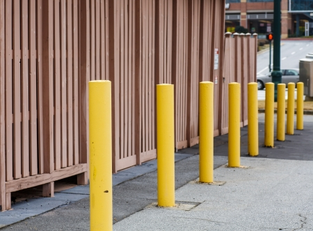 distance: Yellow Metal posts descending into distance by brown wall