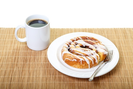cinammon: A fresh baked cinammon roll on a white plate on placemat with fork and a cup of coffee