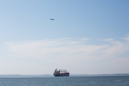 A dredging ship anchored in a harbor and working on the shipping lane photo