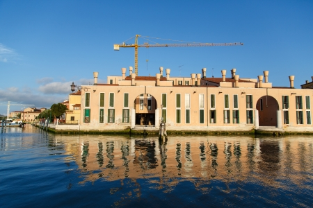 Yellow crane over building in Venice with reflection in blue canal under blue skies photo