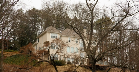 wooded: A nice stucco home on a wooded hillside in the winter