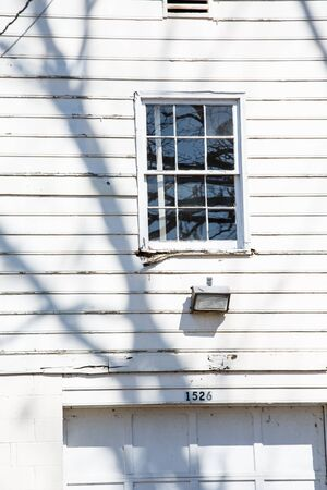 Paint peeling off an old white wooden house with broken window