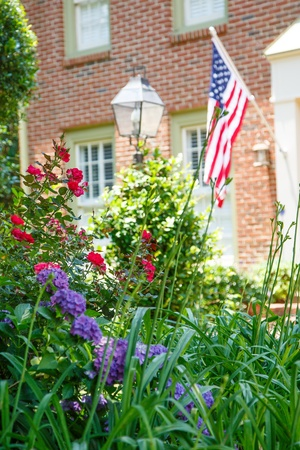 fourth of july: An American flag on a nice brick house with a lush spring garden in front Stock Photo