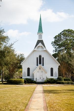 Een kleine witte, houten kerk down trottoir onder mooie hemel