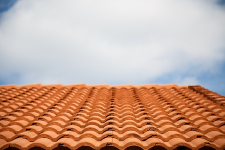 A roof of red clay tiles in rows under a cloudy sky Stock Photo - 20764456