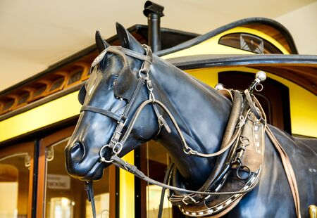 blinders: A statue of a black work horse by an old train car