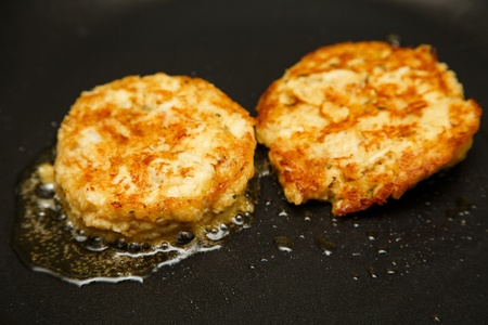 patty cake: Two crab cakes frying in a saute pan in hot oil