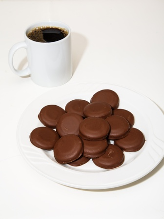 A white plate of chocoloate covered mint cookies with a white mug of coffee