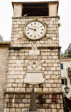 Old clock on an ancient brick wall in Kotor, Montenegro photo