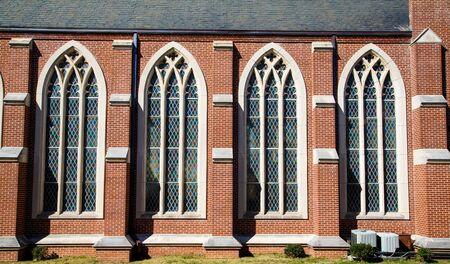 vetrate colorate: Quattro vetrate in una chiesa in mattoni Archivio Fotografico